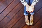 Woman holding in hands cup of coffee with milk sitting on the wooden floor, top view point