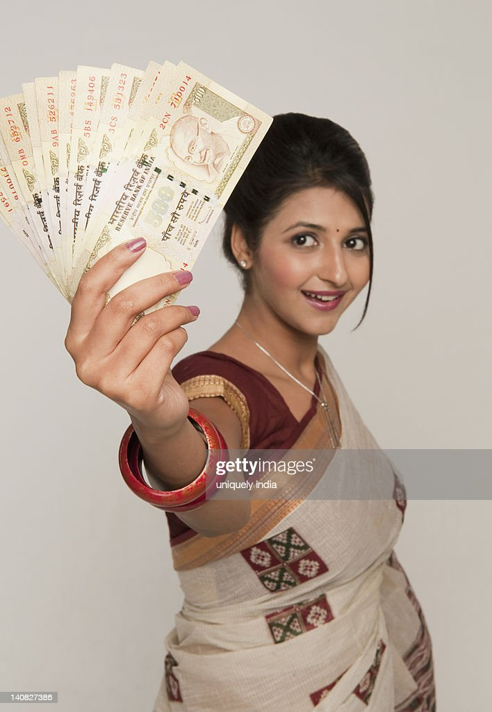 Woman holding Indian five hundred rupee notes and smiling : Stock Photo