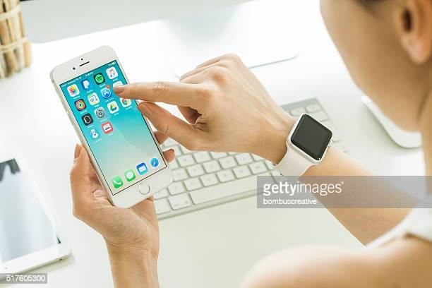 Mulher a segurar iPhone 6s sobre a mesa
