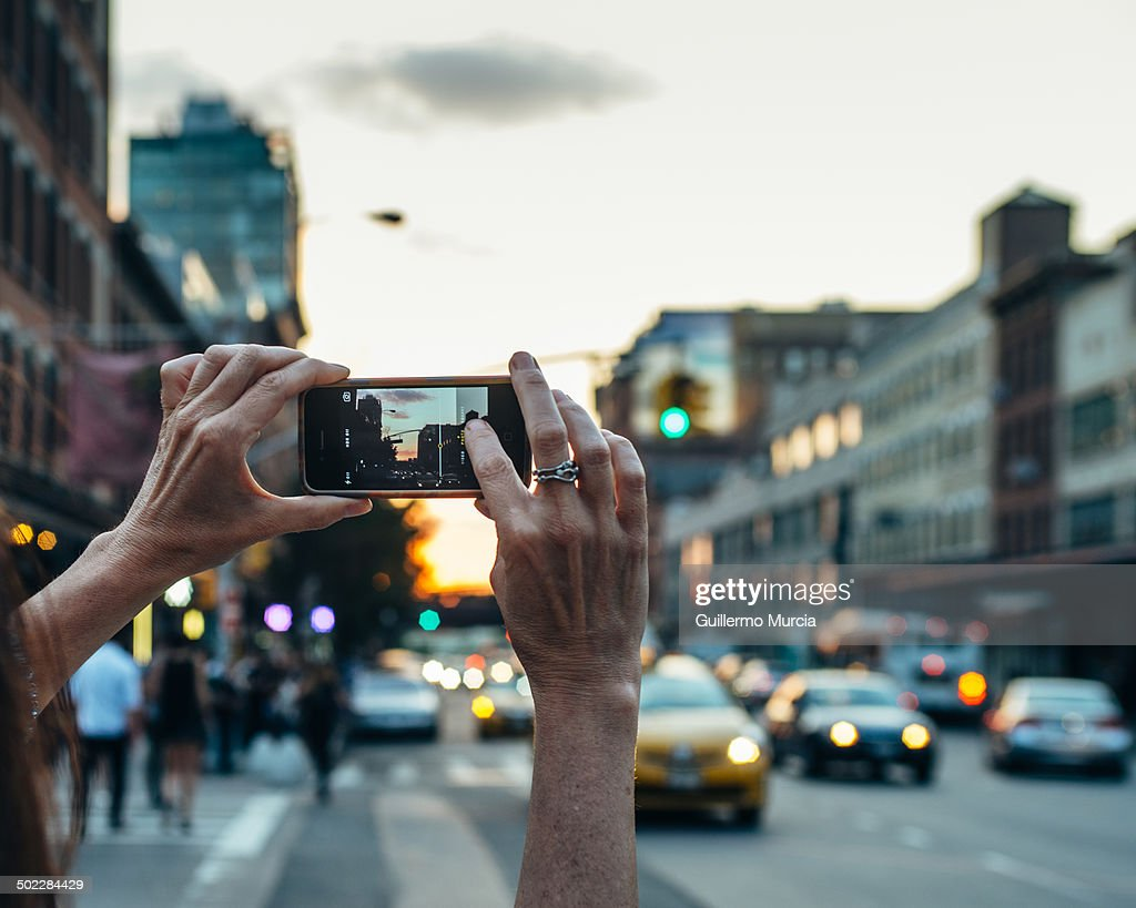Woman holding iPhone photographing a preManhattanhenge at 23rd street in Chelsea