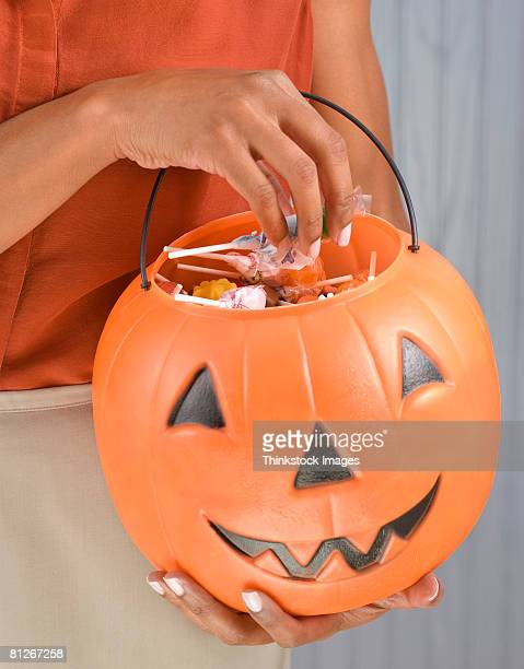 Woman holding jack-o-lantern bucket with candy