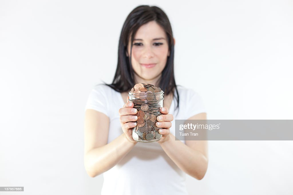 woman holding jar full of coins : Stock Photo