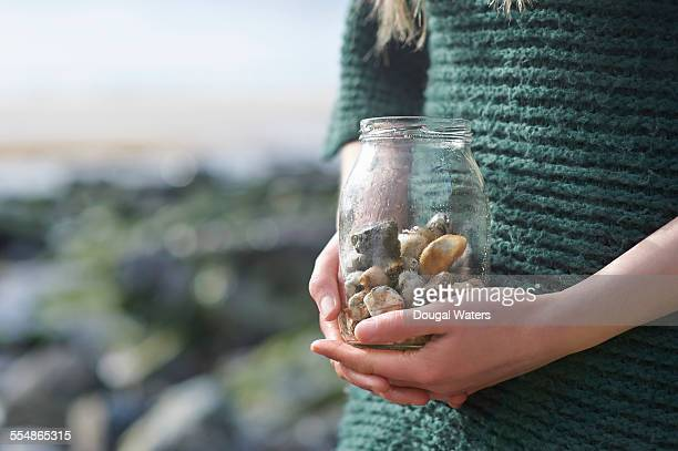 Woman holding jar of pebbles, close up.