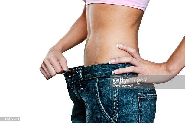 Woman holding jeans open to represent amount of weight loss