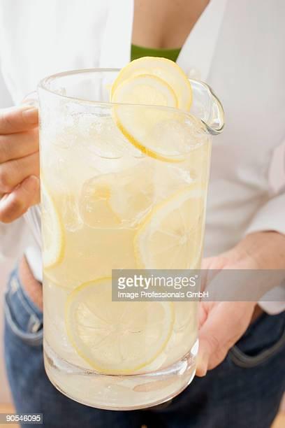 Woman holding jug of lemonade, close up