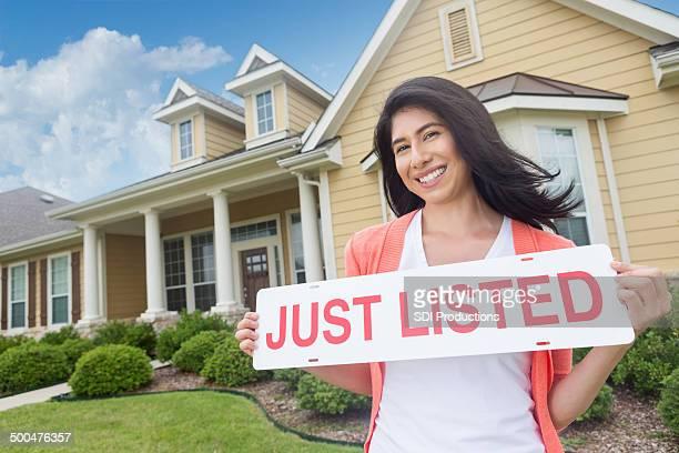 'just listed'サインを持つ女性の前で、美しい家