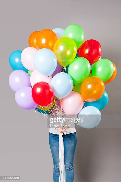 Woman holding large amount of balloons