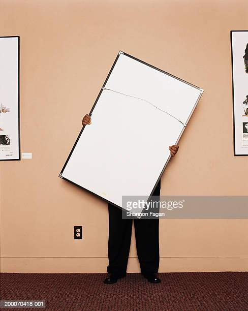 Woman holding large picture in office