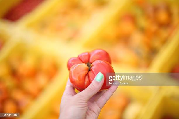 Woman holding large red tomato at farmers market