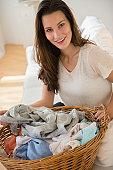 Woman holding laundry basket, smiling