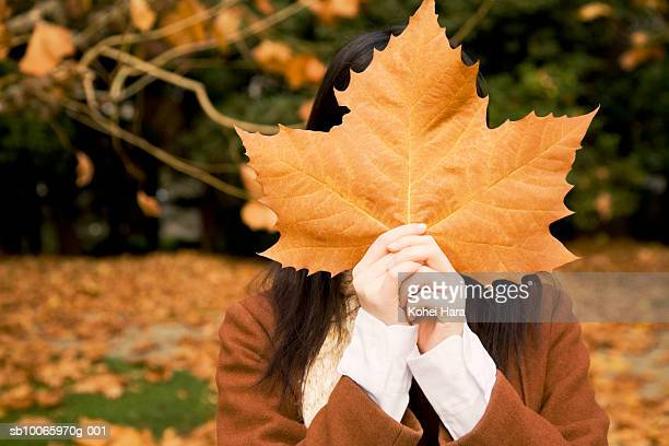 Woman holding leaf in front of face