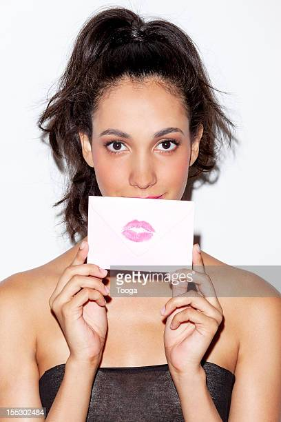 Woman holding letter with lip imprint