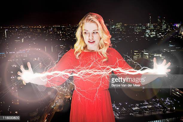 woman holding lightbeams between hands.