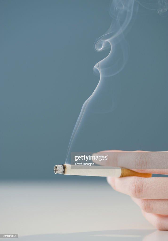 Woman holding lit cigarette