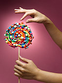 Woman holding lollipop decorated with pills, close-up of hands