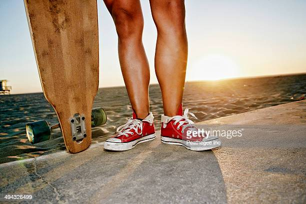 Woman holding longboards on beach