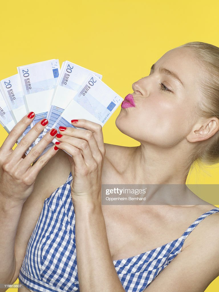 Woman holding lots of money and kissing it : Stock Photo