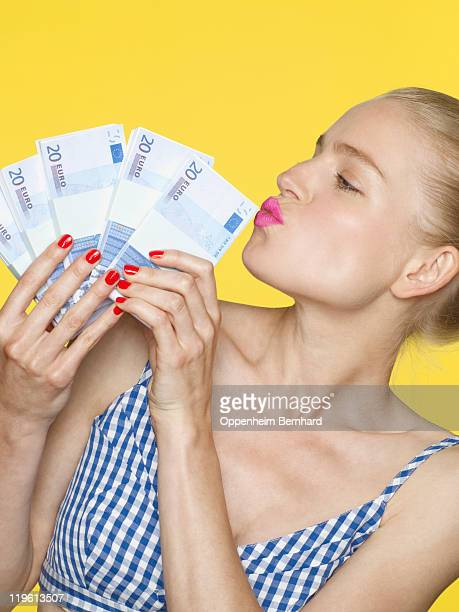 Woman holding lots of money and kissing it