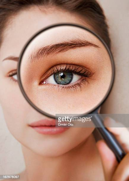 Woman holding magnifying glass in front of her eye