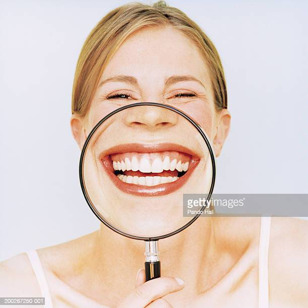 Woman holding magnifying glass in front of mouth, smiling, portrait