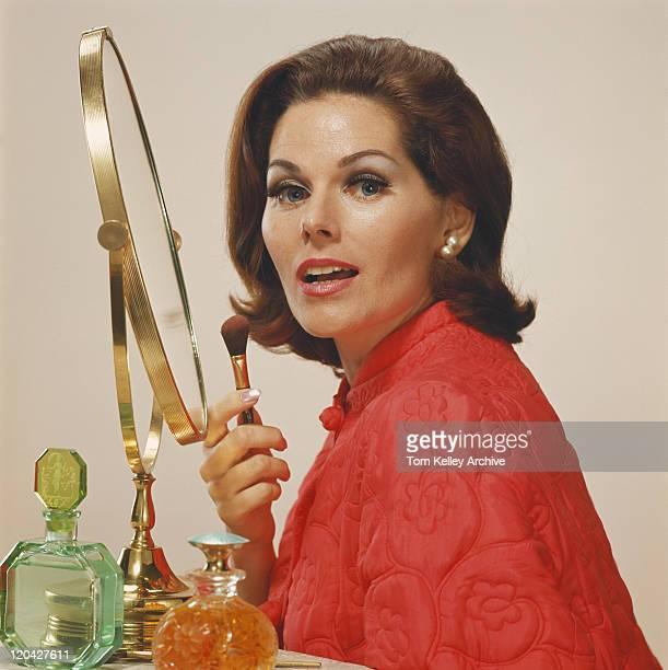 Woman holding makeup brush, portrait