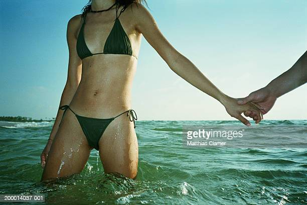 Woman holding man's hand standing in water, mid-section view.