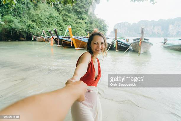 Woman holding man's hand to follow her