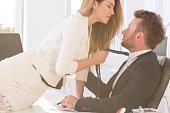 Shot of a beautiful woman sitting on a desk in an office and holding elegant man's tie