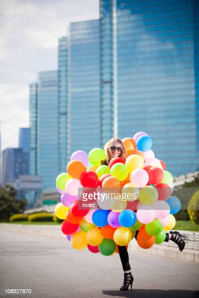 Woman holding many balloons