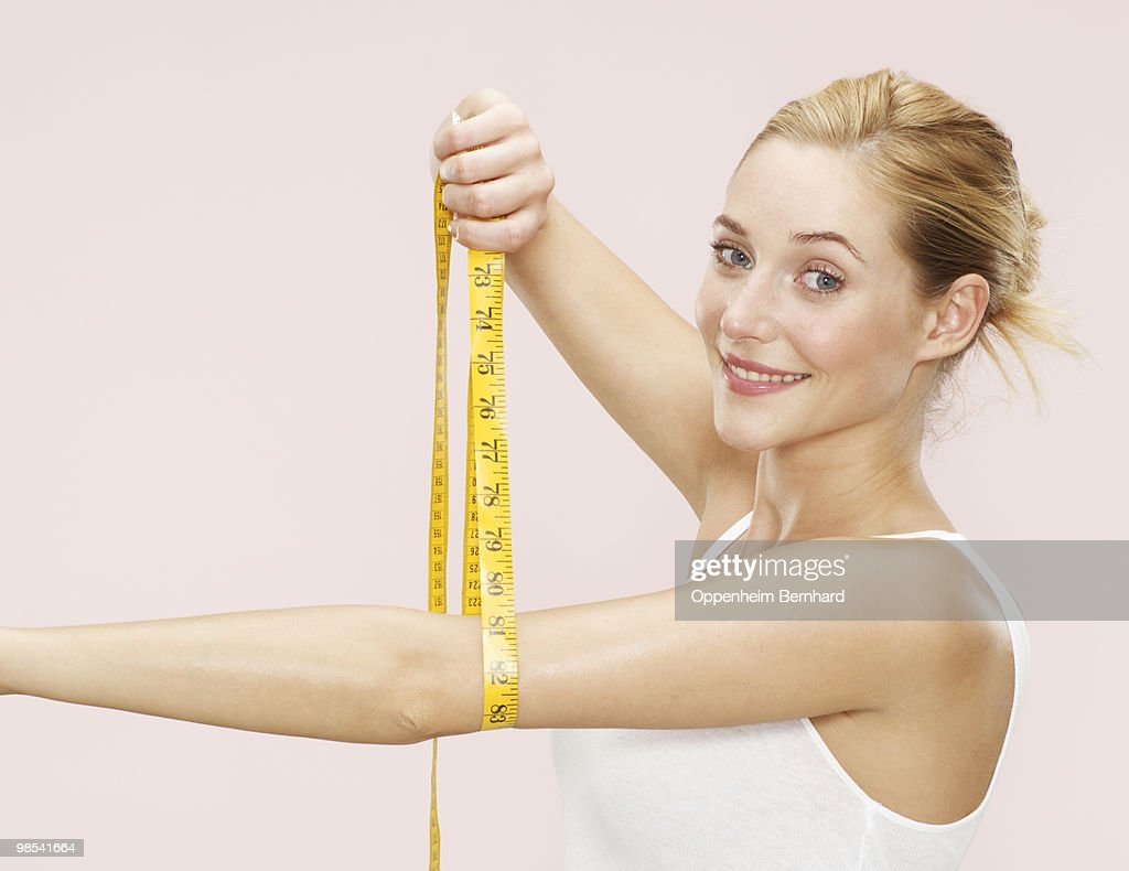 woman holding measuring tape around her arm : Stock Photo