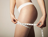 Woman holding measuring tape around thigh, mid section, side view