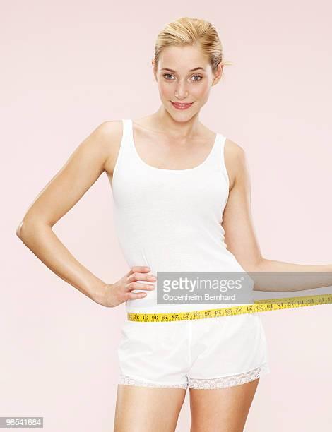woman holding measuring tape around waist