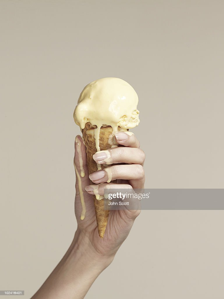 Woman holding melting ice cream cone : Stock Photo