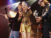 Woman holding microphone flanked by men playing guitars, smiling