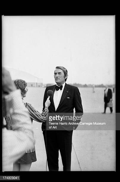 Woman holding microphone to actor Gregory Peck at airport Allegheny County Pennsylvania September 1971
