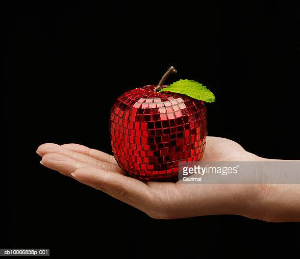Woman holding mirrored apple in palm, close-up