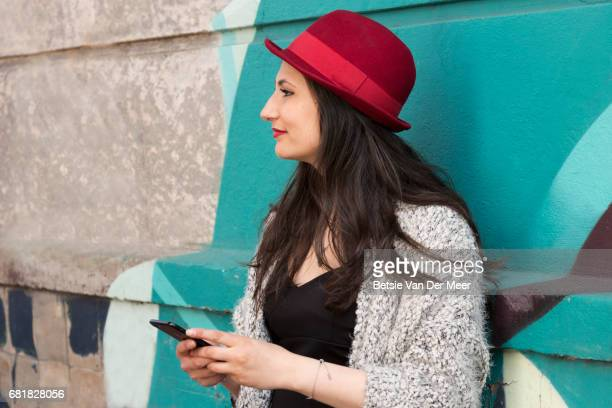 Woman holding mobile phone, standing against colourful wall in urban street.