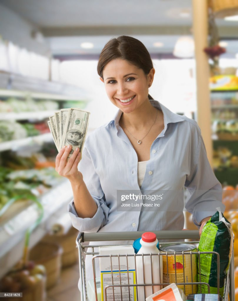 Woman holding money and shopping in grocery store : Stock Photo