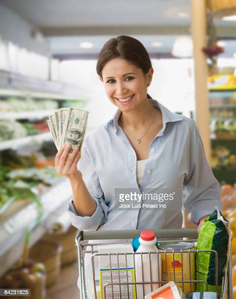 Woman holding money and shopping in grocery store