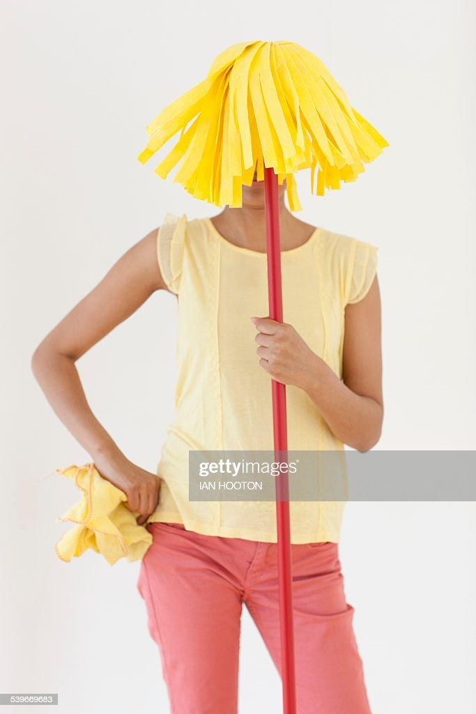 Woman holding mop in front of face