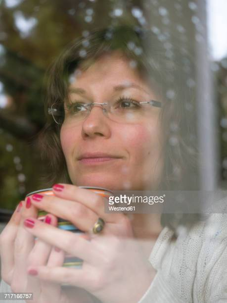 Woman holding mug looking out of window