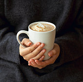 Woman holding mug of hot chocolate with melted marshmallows, mid section, close-up