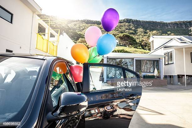 Woman holding multi colored balloons out of a car