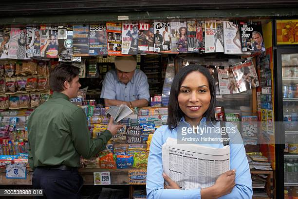 Woman holding newspaper in front of kiosk, smiling
