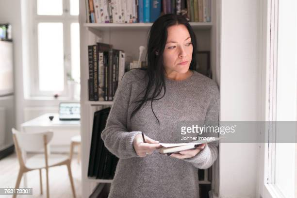 Woman holding note pad, looking through window
