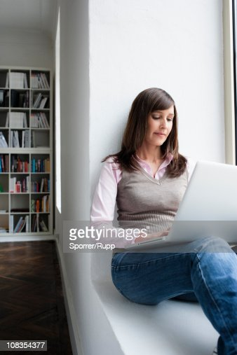 Woman holding notebook on lap : Bildbanksbilder