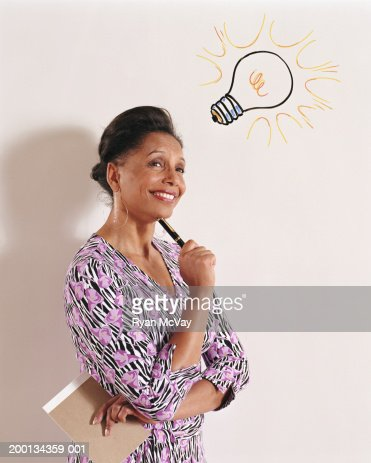 Woman holding notepad and pen, illustrated lightbulb above head : Stock Photo