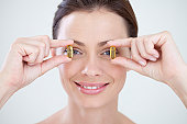 Woman holding oil capsules in front of eyes