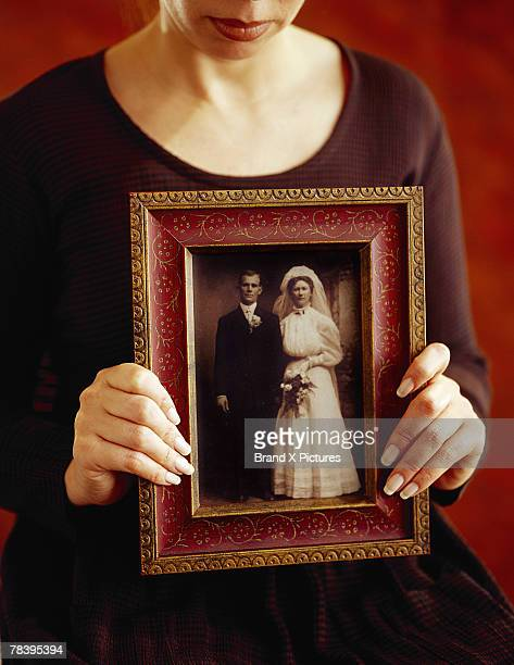 Woman holding old-fashioned wedding photo