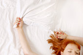 woman holding on to pillow in bed